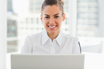 Portrait of a frizzy haired smiling woman working with a laptop