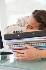 Businesswoman sleeping on a lot of files