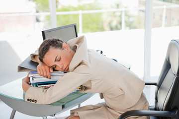 Businessperson sleeping on a lot of files