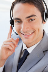 Portrait of a happy businessman talking with a headset