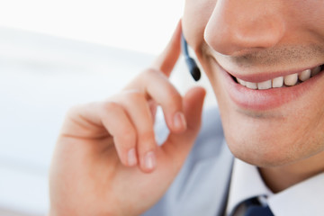 Close-up of a smiling man's mouth talking with a headset