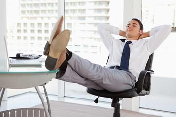 Happy businessman feet on his desk