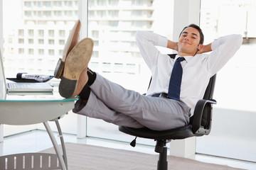 Portrait of a businessman feet on his desk