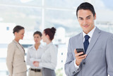 Smiling businessman with cellphone and colleagues behind him