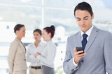 Businessman reading text message with associates behind him