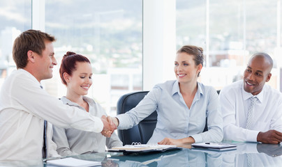 Businesspeople shaking hands while sitting at a table