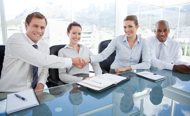 Smiling businesspeople shaking hands while sitting at a table
