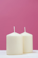 Un par de velas sobre fondo rosa