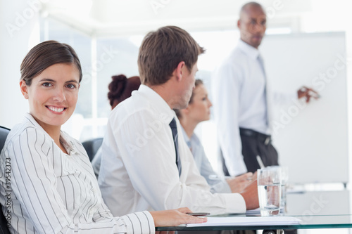 Smiling saleswoman with presentation being held behind her