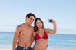 Attractive couple in swimsuit taking a picture together