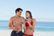 Couple in swimsuit laughing while looking their picture