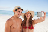 Smiling couple in swimsuit taking a picture together