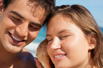 Close-up of a couple listening to a seashell