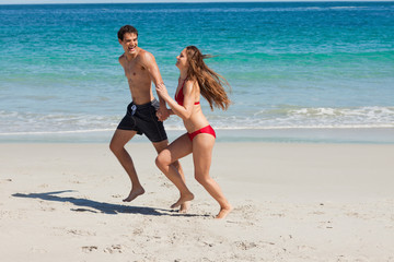 Funny lovers running on the beach