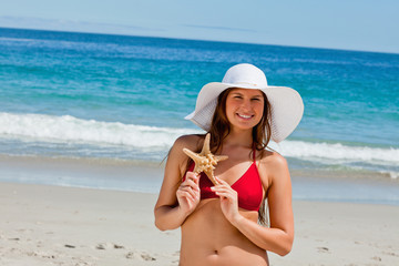 Portrait of a woman wearing a hat and holding a starfish