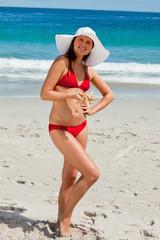 Portrait of an attractive woman in bikini holding a starfish
