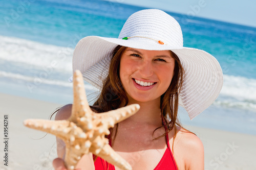Portrait of a smiling woman showing a starfish