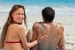 Portrait of a woman applying sunscreen in form of heart on her boyfriend