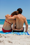 Rear view of a tanned duo in love sitting on a beach towel