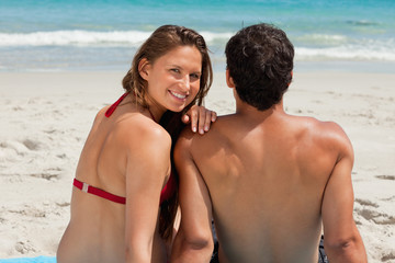 Portrait of a woman sitting on a beach towel with her boyfriend