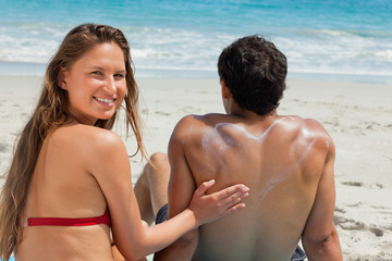 Portrait of a woman applying sunscreen in form of heart on her boyfriend