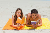 Tanned couple reading a book
