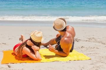 Couple being tanning watching something