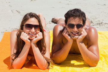 Portrait of a cute couple being tanning on the beach