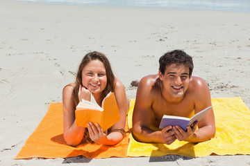 Portrait of a tanned couple reading a book