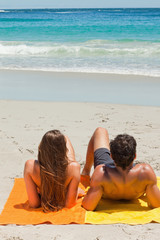 Tanned young couple lying on the beach