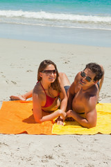 Portrait of a tanned young couple lying on the beach