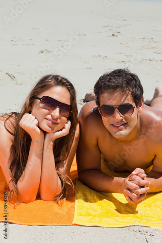 Portrait of a couple being tanning on the beach