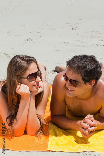 Close-up of a couple being tanning on the beach
