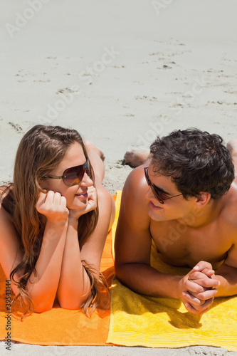 Close-up of a young couple being tanning on the beach