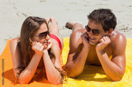 Close-up of a tanned couple lying on the beach
