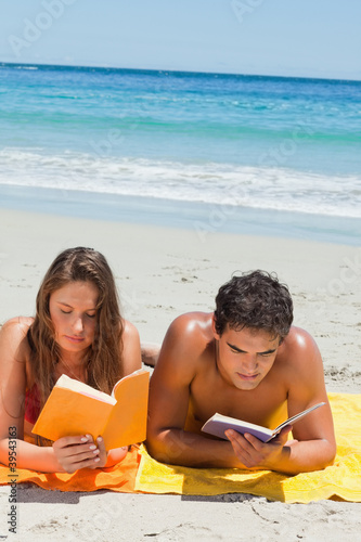 Tanned couple reading a book while lying on the beach