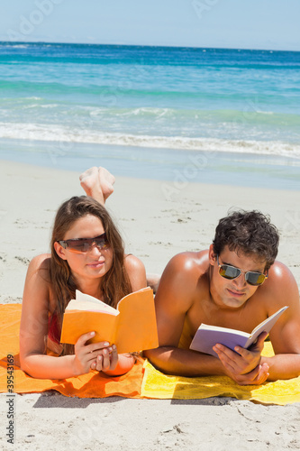 Couple with sunglasses reading a book while lying on the beach