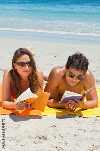 Tanned couple reading a book on the beach