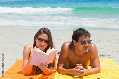 Tanned couple on the beach with the woman reading