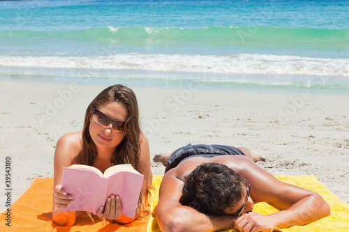 Tanned duo on the beach with the woman reading
