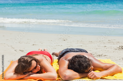 Tanned couple sleeping on the beach