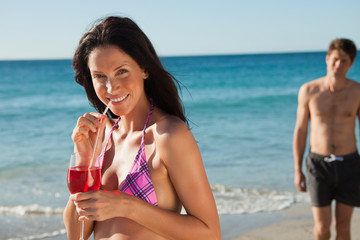 Woman drinking a cocktail while standing by the water