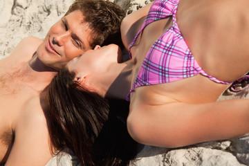 Close-up of a couple lying on a sandy beach