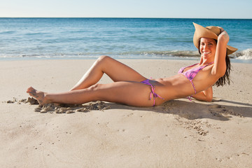 Portrait of a gorgeous female in bikini lying on the sand