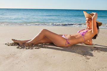 Gorgeous female in bikini  lying on the sand