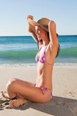 Thin female in bikini sitting on the sand