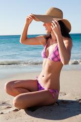 Smiling female in bikini sitting on the sand