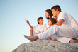 Family sitting on a natural stone wall together as the son points in front of him