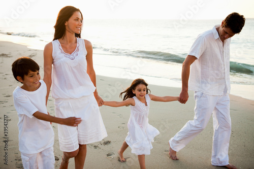 Cute family walking hand in hand at sunset time