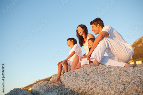 Family sitting on rocks while looking into the distance